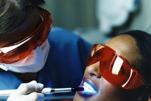 Dentist Examining a Woman's Teeth With Ultraviolet Light